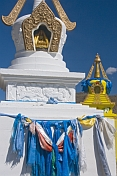 caption: White and yellow Dagobas with blue prayer scarves at the Singino monastery.