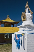 White Dagoba with blue prayer scarves and yellow wooden temple at the Singino monastery.