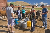 Mongolian villagers filling water cans from a communal hose.