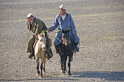 Two Mongolian horsemen crossing a gravel desert plain near the Khyargas Nuur lake, near Naranbulag.
