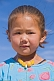 Image of Small Mongolian girl in a blue top and yellow beads.