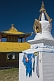 Image of White Dagoba with blue prayer scarves and yellow wooden temple at the Singino monastery.
