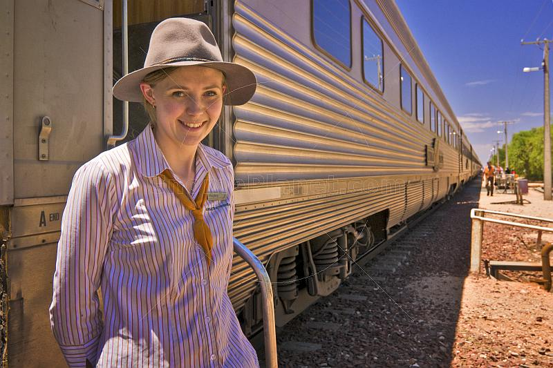 Great Southern Rail female attendant in hat next to Indian Pacific carriages.
