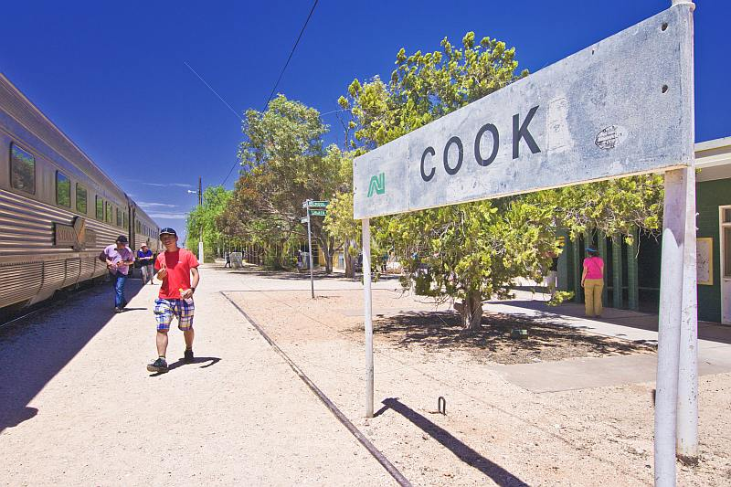 Passengers from Indian Pacific train walk past Cook railway station signboard.