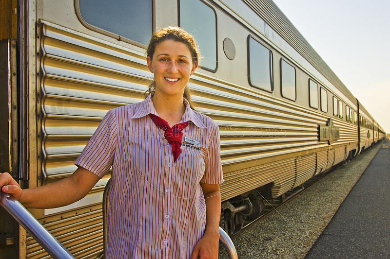 Smiling Great Southern Rail female attendant next to Ghan train carriages at Alice Springs station.