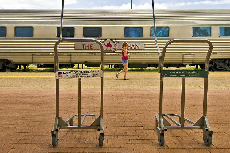 Young female tourist and empty luggage carriers at Alice Springs station.