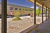 Indian Pacific passengers walk beside train carriages at Cook railroad station.