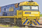 Yellow and blue Ghan locomotive waiting at Alice Springs railway station.