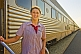 Image of Smiling Great Southern Rail female attendant next to Ghan train carriages at Alice Springs station.