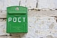 Image of Green post-box on a whitewashed wall.