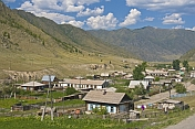 caption: Small Russian village of log houses nestles between the Altai Mountains.