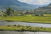 Small Russian town of log houses nestles between the Altai Mountains and the river.