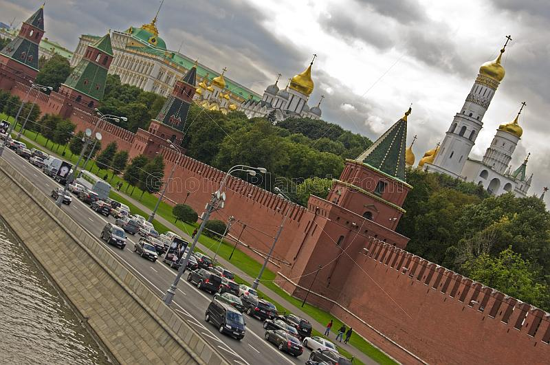Traffic passes the red walls of the Kremlin, alongside the Moscow River.