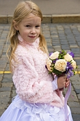Young blonde Russian girl dressed as a bridesmaid holds a bunch of flowers on Red Square.