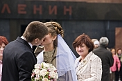 A young Russian couple, just married, kiss in front of Lenin's Tomb, on Red Square.