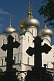 Image of The sharp black silhouettes of two tombstones in the shape of crosses contrast the gold crosses on the Smolensk cathedral at the Novodevichy Convent.