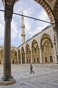 Man walks across courtyard of Sultan Ahmet\\\\'s blue mosque in Sultanahmet.