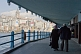 Image of Elderly couple walk on lower deck of the Galata Bridge, to cross the Golden Horn.
