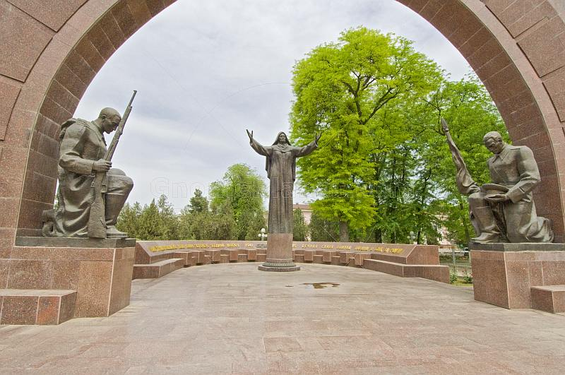 Statues of 2 kneeling soldiers guard the Soviet war memorial with its central statue of the Crying Mother.