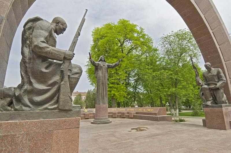 Statues of 2 kneeling soldiers guard the Soviet war memorial with its eternal flame.