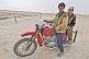 Two Turkman desert dwellers on a motorbike at the Darvaza Water Crater.