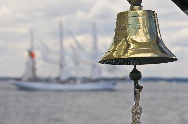 Ships bell of the barque 'Picton Castle' with tallship 'Sagres' in background.