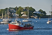 A lobster boat passes moored sailboats as it returns to harbor in the early morning.