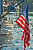 U.S.A. flag 'Stars and Stripes' hangs from boom on sailing ship in harbour.