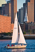 J-Class boat 'Whiplash' sails through Boston harbor in late evening.
