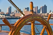 Ships wheel of the barque 'Picton Castle' against a background of Boston Harbor.