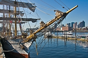 Bows and rigging of the barque 'Picton Castle' against a background of Boston Harbor.