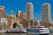 Ships and boats of many types fill the inner harbor, backed by tall office buildings.
