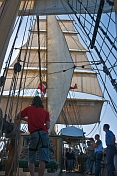Crew stand on deck of the barque 'Picton Castle' under full sail leaving Boston harbor.