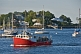 Image of A lobster boat passes moored sailboats as it returns to harbor in the early morning.