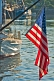 Image of U.S.A. flag 'Stars and Stripes' hangs from boom on sailing ship in harbour.