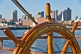 Image of Ships wheel of the barque 'Picton Castle' against a background of Boston Harbor.