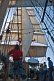 Image of Crew stand on deck of the barque 'Picton Castle' under full sail leaving Boston harbor.