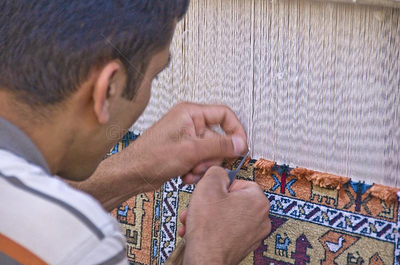 Uzbek carpet weaver knots another thread to his silk rug.