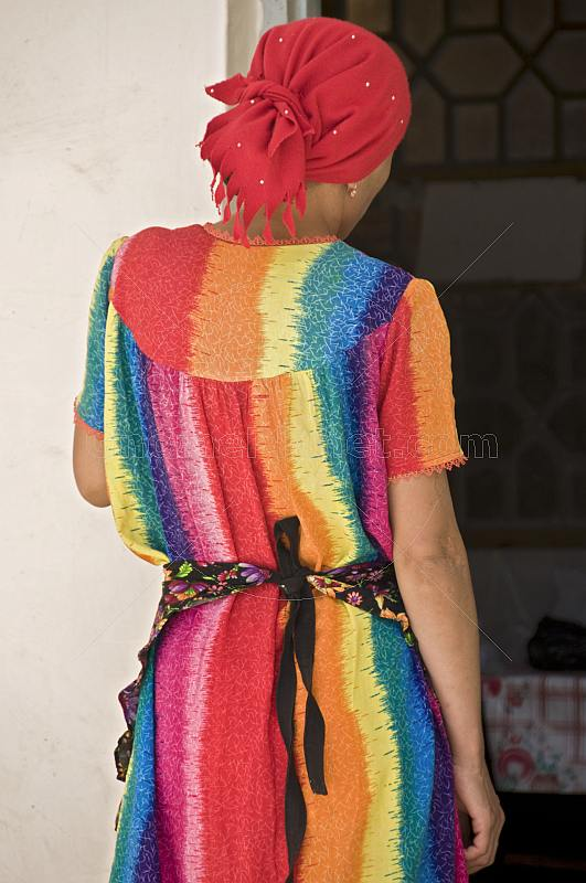 Bright colours of a dress worn by a lady trader in the bazaar.