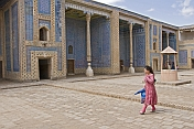 Young woman walks across the courtyard of the Tosh-Hovli Palace.