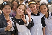 Smiling school Children in traditional black and white uniforms greet visitors from abroad.