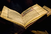 Pages of an ancient Koran, on a stand.