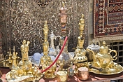 Carpets, rugs, brass-work, silver coffee sets, and water pipes for sale in bazaar.