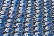 Trader\\'s display of blue and white pottery bowls tempts the traveller in Bukhara\\'s Central Asian Bazaar.