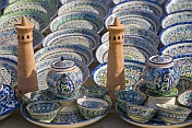 Ceramic minatures of the Kalon Minaret contrast the blues and greens of pottery bowls and plates.