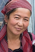 caption: Uzbek lady silk weaver in red headscarf.