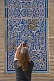 Image of Tourist woman photographs some blue glazed ceramic tilework on the Mohammed Amin Khan Medressa.