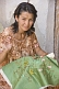 Image of Craftswoman demonstrates her skill with embroidery.
