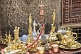 Image of Carpets, rugs, brass-work, silver coffee sets, and water pipes for sale in bazaar.