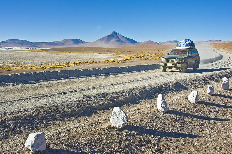Toyota 4WD drives a gravel road next to the Laguna Colorada salt lake.